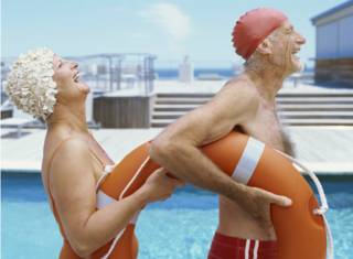 Dos adultos mayores celebrando en una piscina