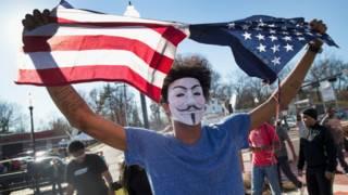 Un joven enmascarado rompiendo una bandera de EEUU