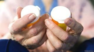 Mujer con frascos de medicamentos en la mano