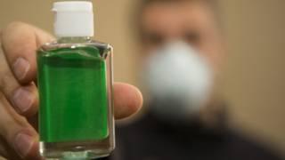 Un hombre sujeta un envase de gel anti bacterial