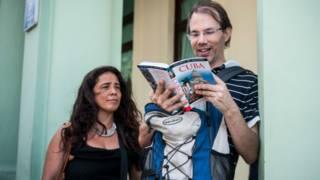 Una pareja de turistas estadounidenses miran un libro de viajes sobre Cuba en La Habana