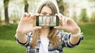 Una joven se toma una auto foto o selfie con su celular