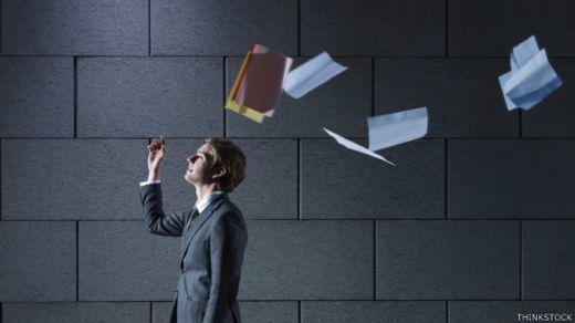 Una persona lanza al aire una carpeta con papeles