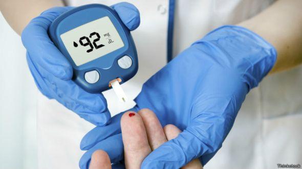 Persona midiendo la glucosa en la sangre con un aparato.