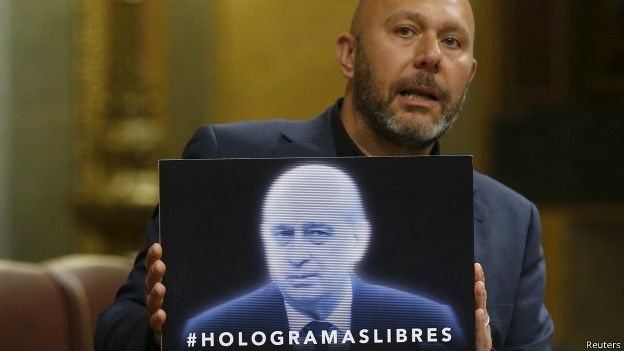 Un diputado de la oposición, sostiene un cartel del ministro de Interior español, Jorge Fernández Díaz, convertido en holograma.