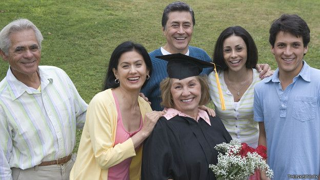 Una graduanda de edad madura junto a su familia