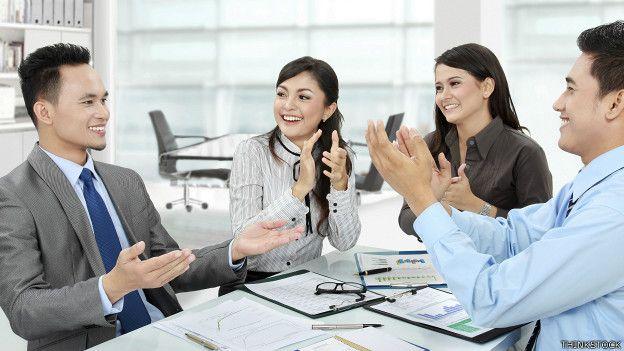 Un trabajador con un grupo de colegas que lo aplauden