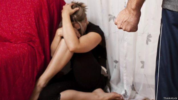 Mujer en el piso amenazada por el puño de un hombre