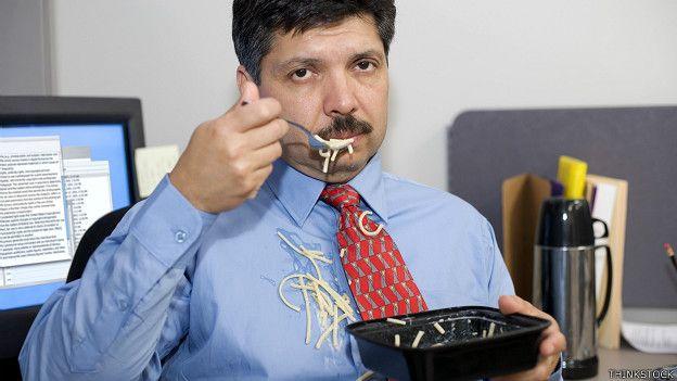 Un ejecutivo comiendo malamente en el escritorio