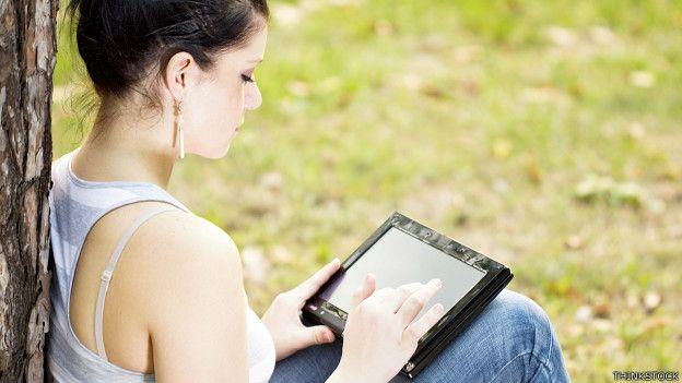 Una joven escribiendo en una tableta