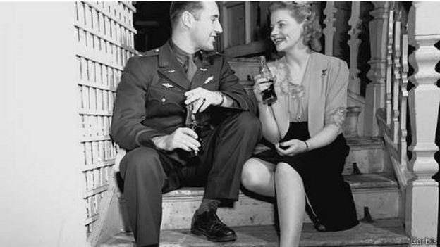 Un soldado con una joven y una botella de Coca-Cola