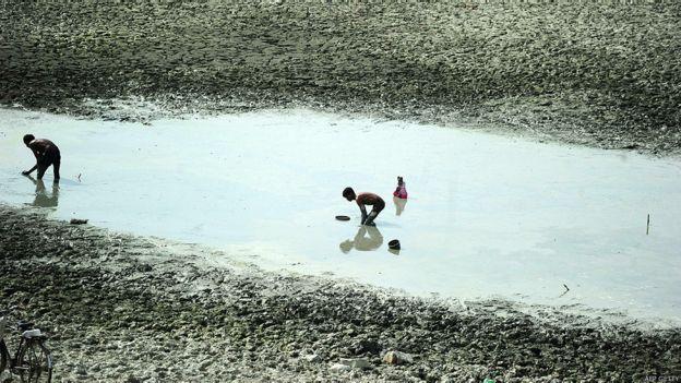 Pescadores intentan pescar en un pequeño lago
