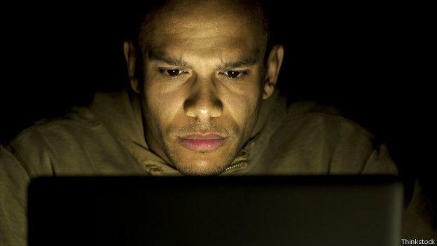 Hombre viendo una computadora.