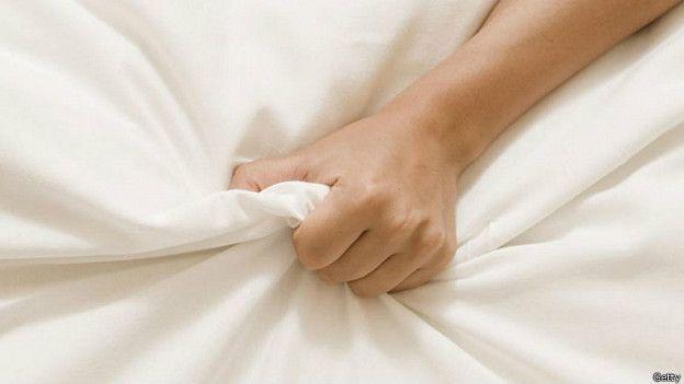 Женская рука, сжимающая простыню