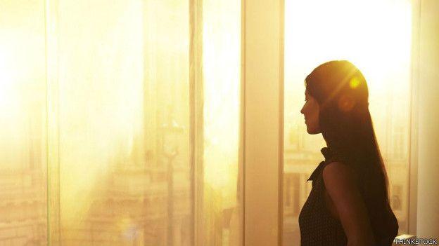 Una persona mira el amanecer en su ventana