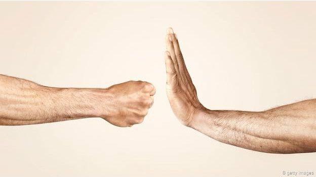 Una persona que va a golpear a otra con el puño