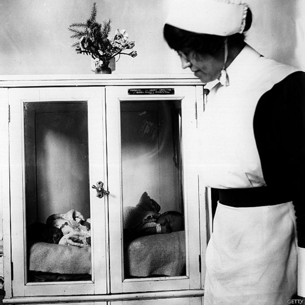 A nurse at Queen Mary Hospital in London cares for two babies in an incubator.  Photo of 1927.
