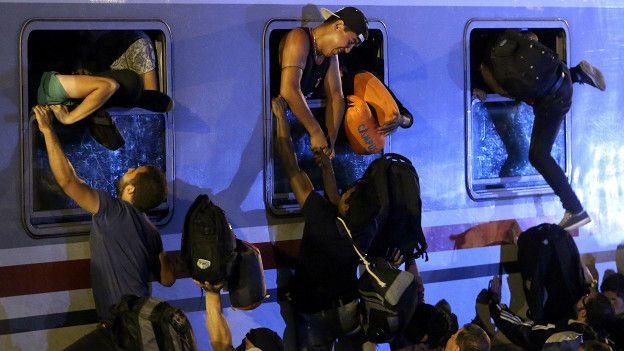 Мигранты залезают в поезд
