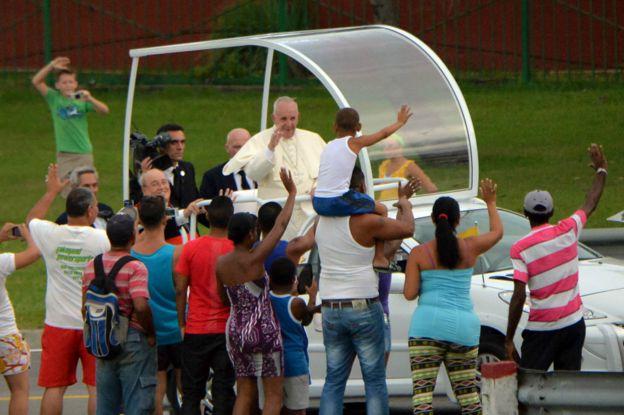 El papa Francisco saluda a personas que esperaban para verlo durante su recorrido.