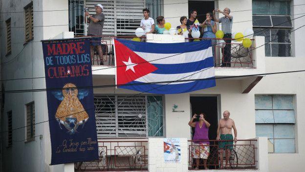 Desde un balcón, unas personas toman fotos del papamovil.