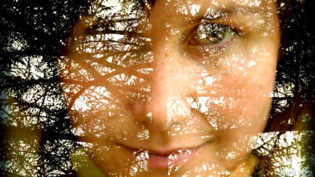 Un rostro fundido con una escena boscosa