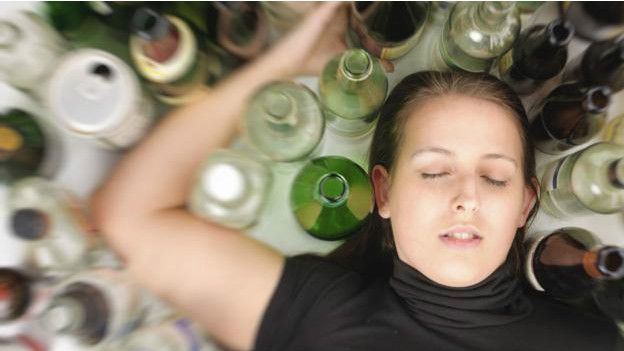 Una persona inconsciente entre muchas copas y vasos