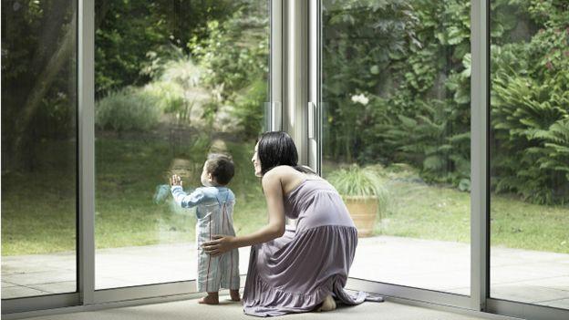 Madre con hijo mirando por la ventana
