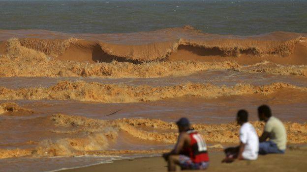 Personas observan el agua de una playa de Brasil cubierta por el barro que se zafó de un dique minero.