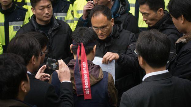 警察向韓相均(中)出示逮捕令(10/12/2015)