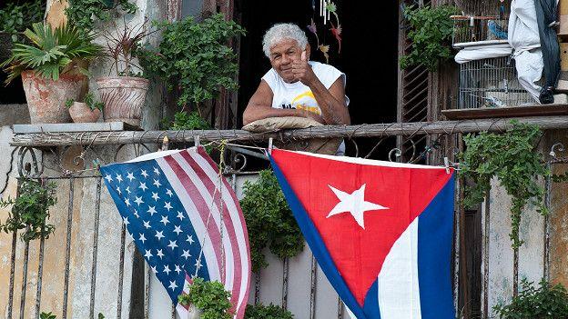 Hombre asomado en una ventana de la que cuelgan las banderas de EE.UU. y Cuba