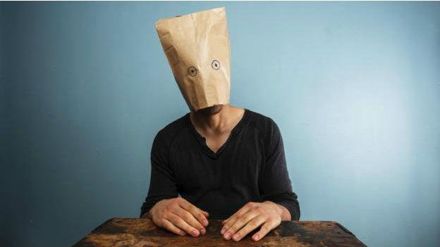 Una persona con una bolsa de papel en la cabeza