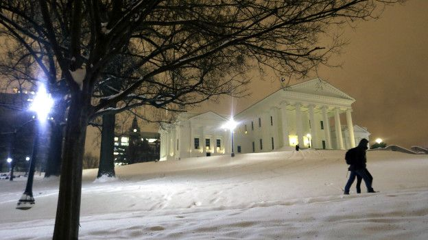 Una pareja camina en la nieve cerca del capitolio de Virginia.