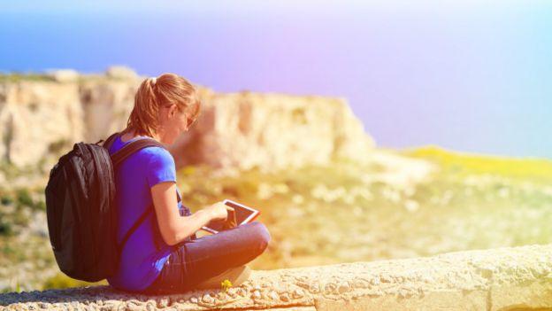 Una joven con una tableta en un lugar abierto