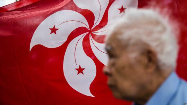 香港特區區旗前的老人(資料照片)