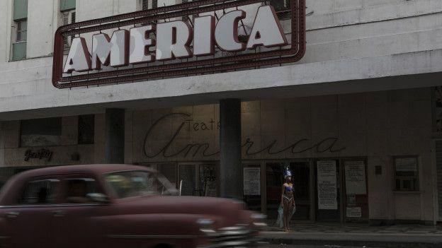 Mujer vestida de vedette frente al teatro America