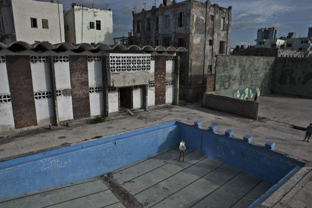 Una mujer posa en vestido de baño dentro de una piscina vacía y abandonada