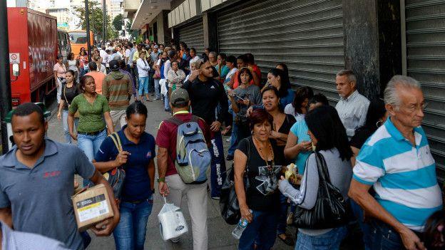 Los venezolanos hacen largas filas fuera de los supermercados para conseguir aliementos.