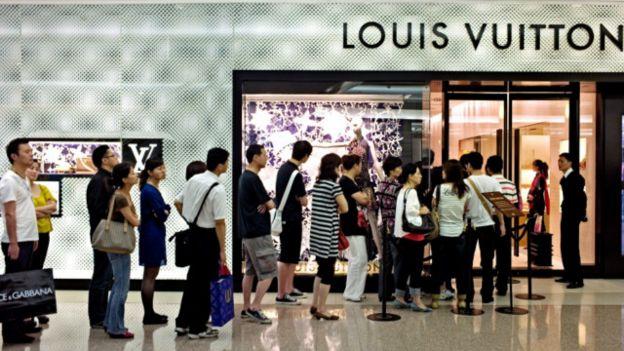 上海一家路易威登专卖店前的顾客。报告预计中国高收入消费者将转向价格更高的优质品牌。