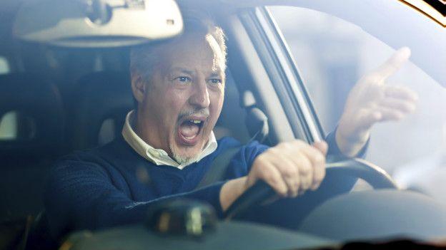 Hombre enojado manejando un auto