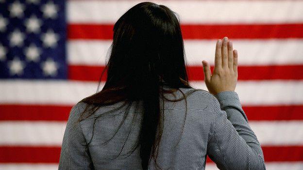 Mujer de espaldas jurando la bandera estadounidense