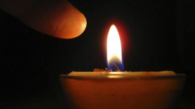 Una persona acercando el dedo a una llama de vela