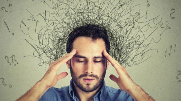 Una persona con ideas enredadas saliéndole de la cabeza