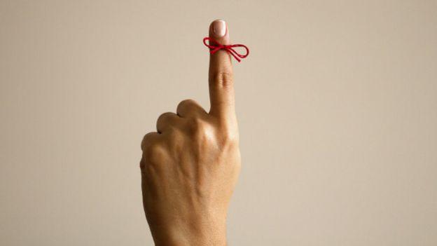 Una persona con un cordón atado en un dedo