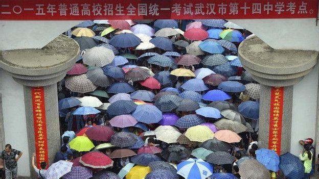 Estudiantes hacen una larga fila para hacer un examen a la entrada de una universidad en la ciudad de Wuhan