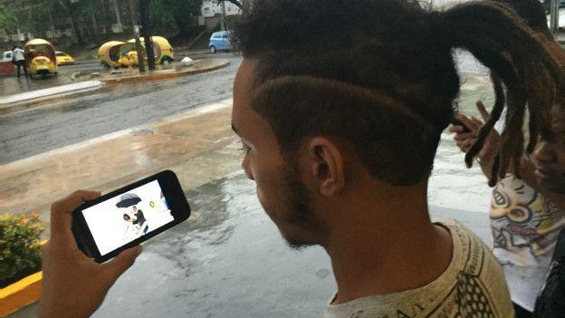 Omar mira la llegada de Obama desde su celular inteligente
