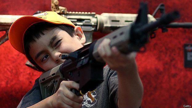 Un niño sostiene un arma durante la exposición anual de la Asociación Nacional del Rifle de EE.UU. (NRA).