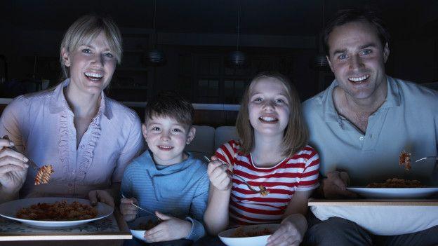 Familia come viendo la tele.