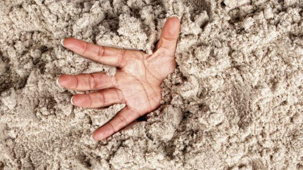 Una mano asomándose en arena movediza