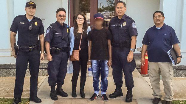 En joven rescatado posa en la foto junto a guardacostas de EE.UU. en Honolulu y con Carolina Ramos, funcionaria de la Cancillería colombiana.