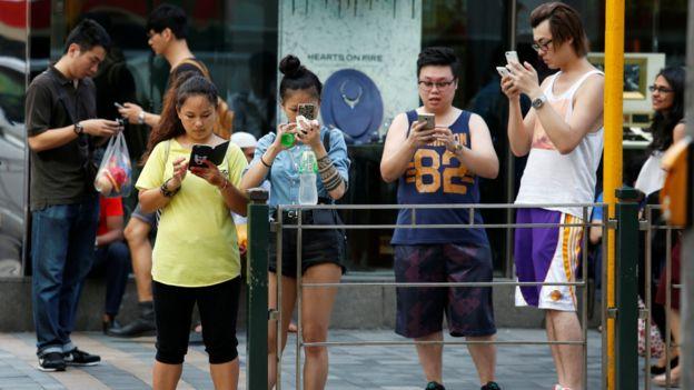 香港街頭朝著馬路抓捕「精靈」的Pokemon Go玩家(26/7/2016)